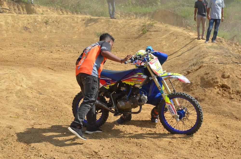 man in orange and blue shirt riding blue and black motocross dirt bike