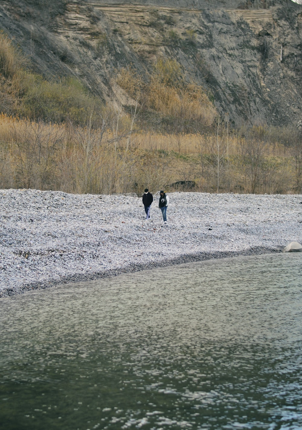 person in black jacket walking on gray sand near body of water during daytime