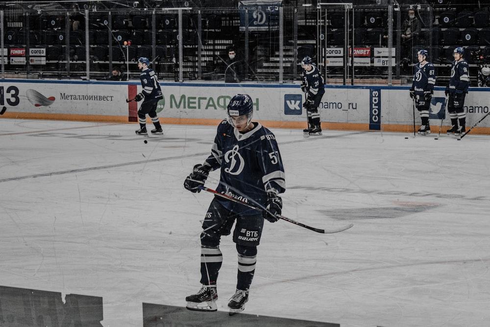 man in black ice hockey jersey playing hockey