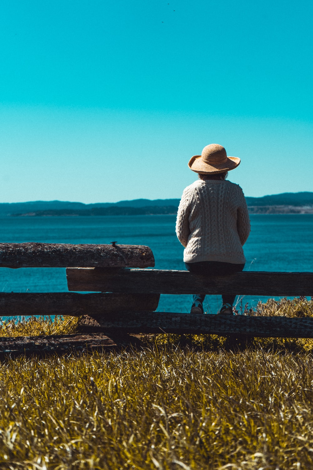 woman in white long sleeve shirt sitting on bench looking at the sea during daytime