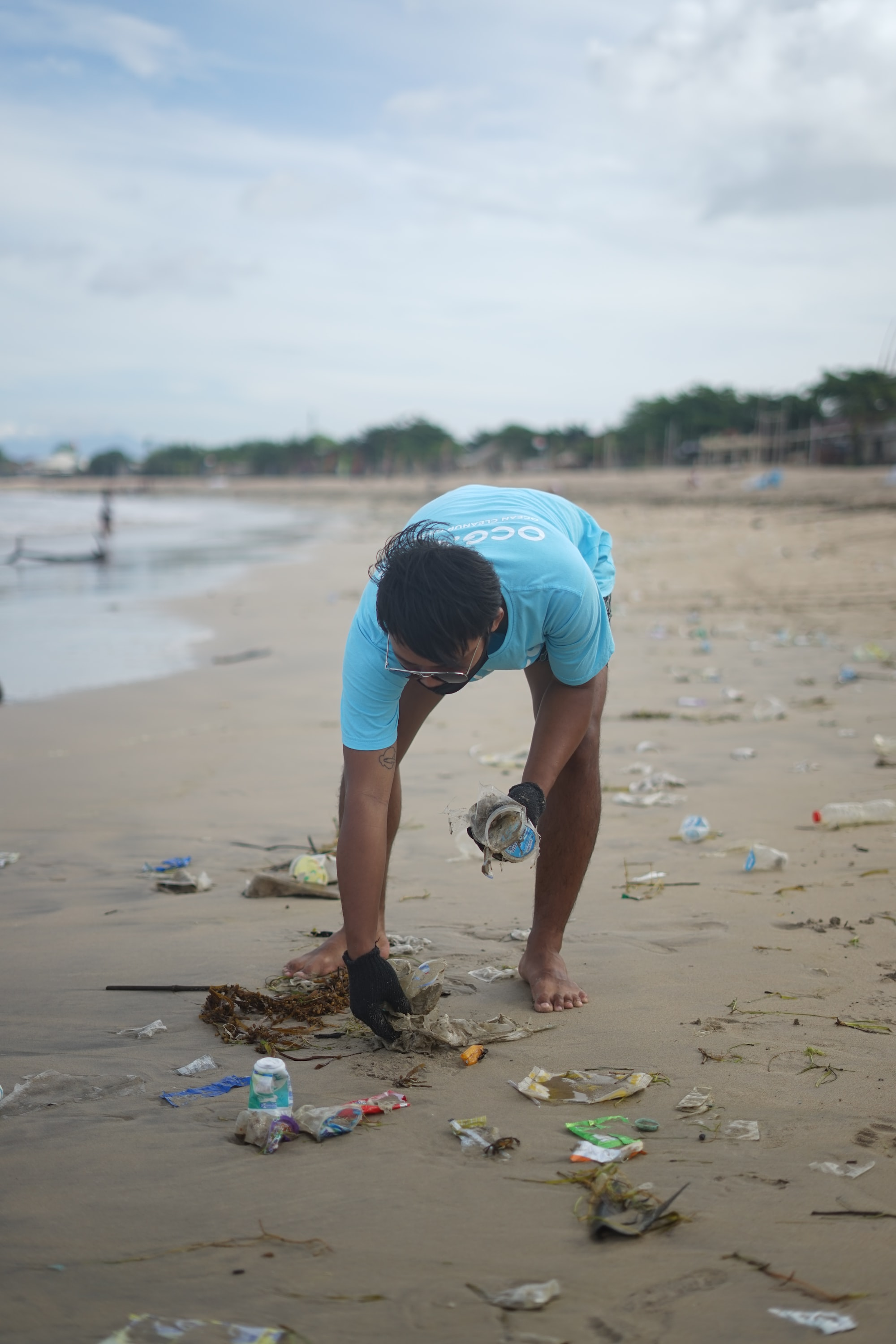 picking up plastic on the beach