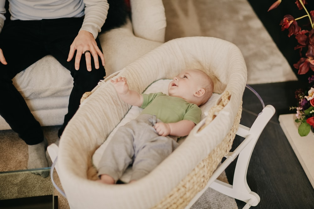 baby in green onesie lying on white and brown crib