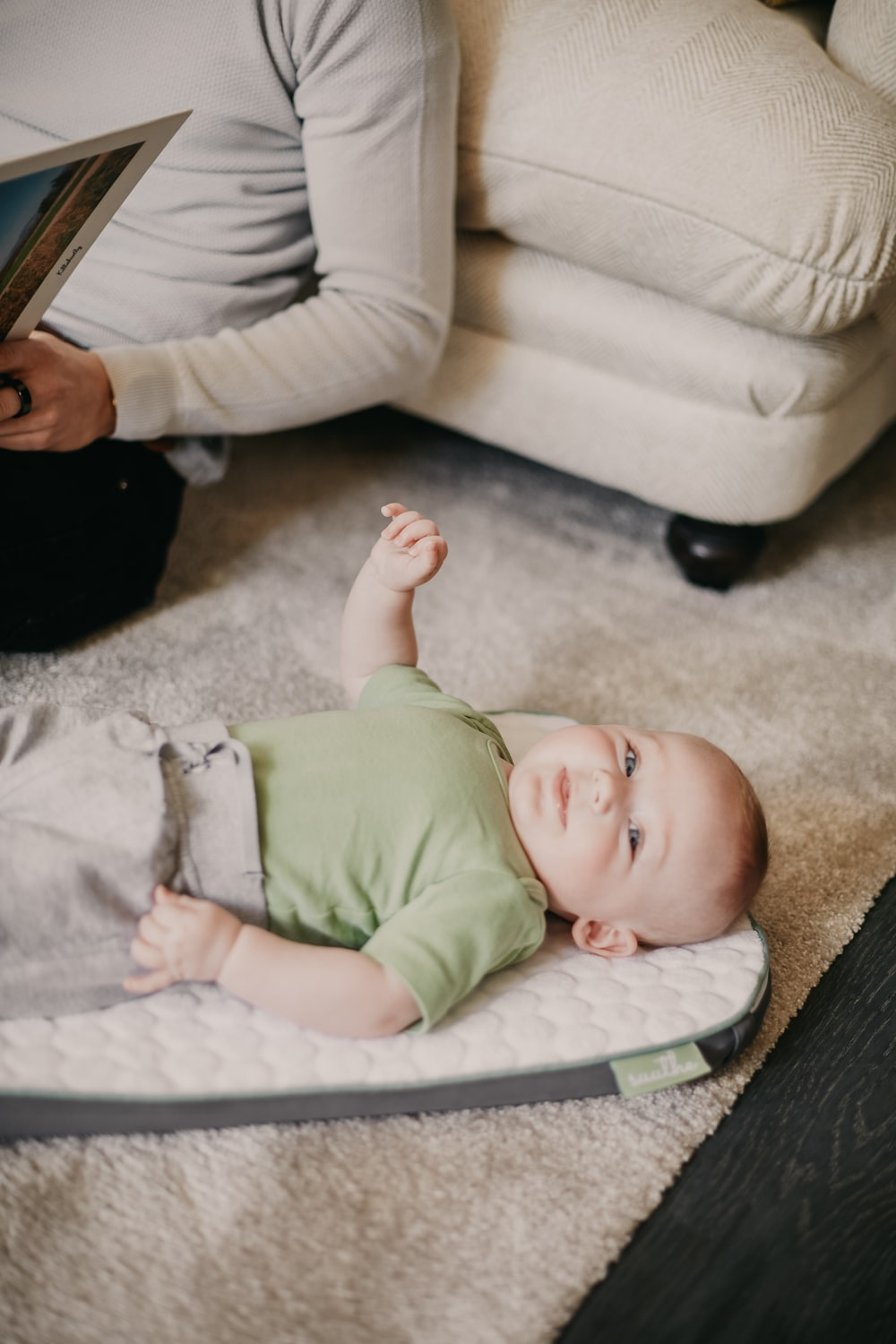 baby in green onesie lying on white textile