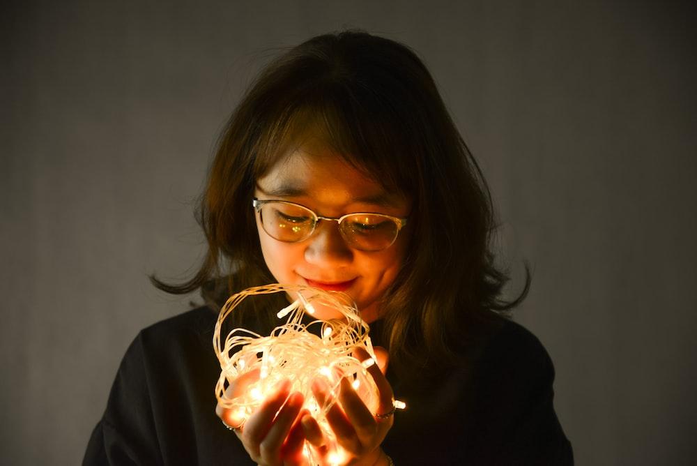 woman in black framed eyeglasses holding lighted candle