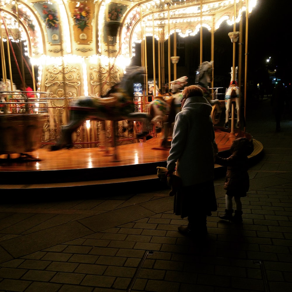 people standing in front of horse carousel during night time