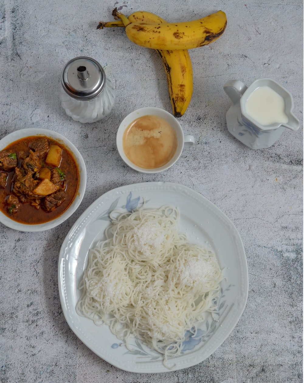 white ceramic plate with pasta and brown sauce