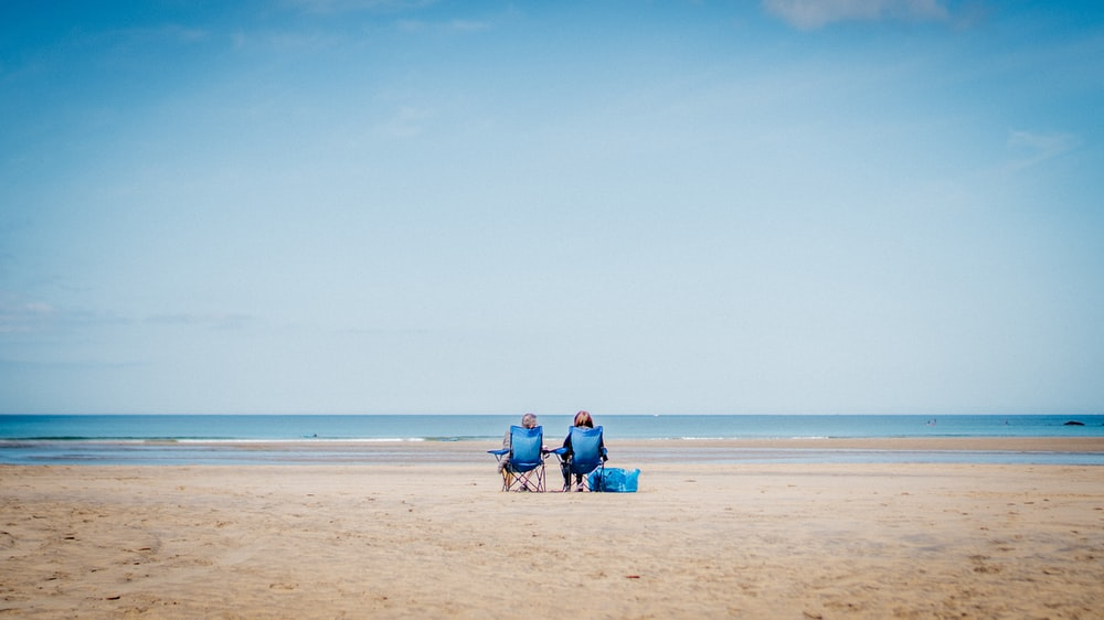 2 person sitting on beach sand during daytime
