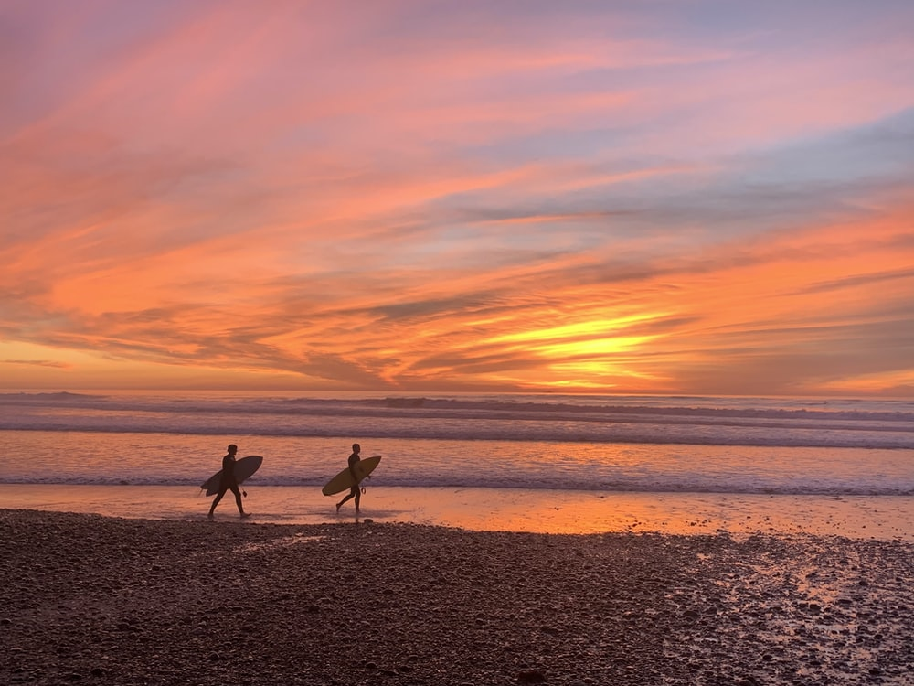 2 people walking on beach during sunset