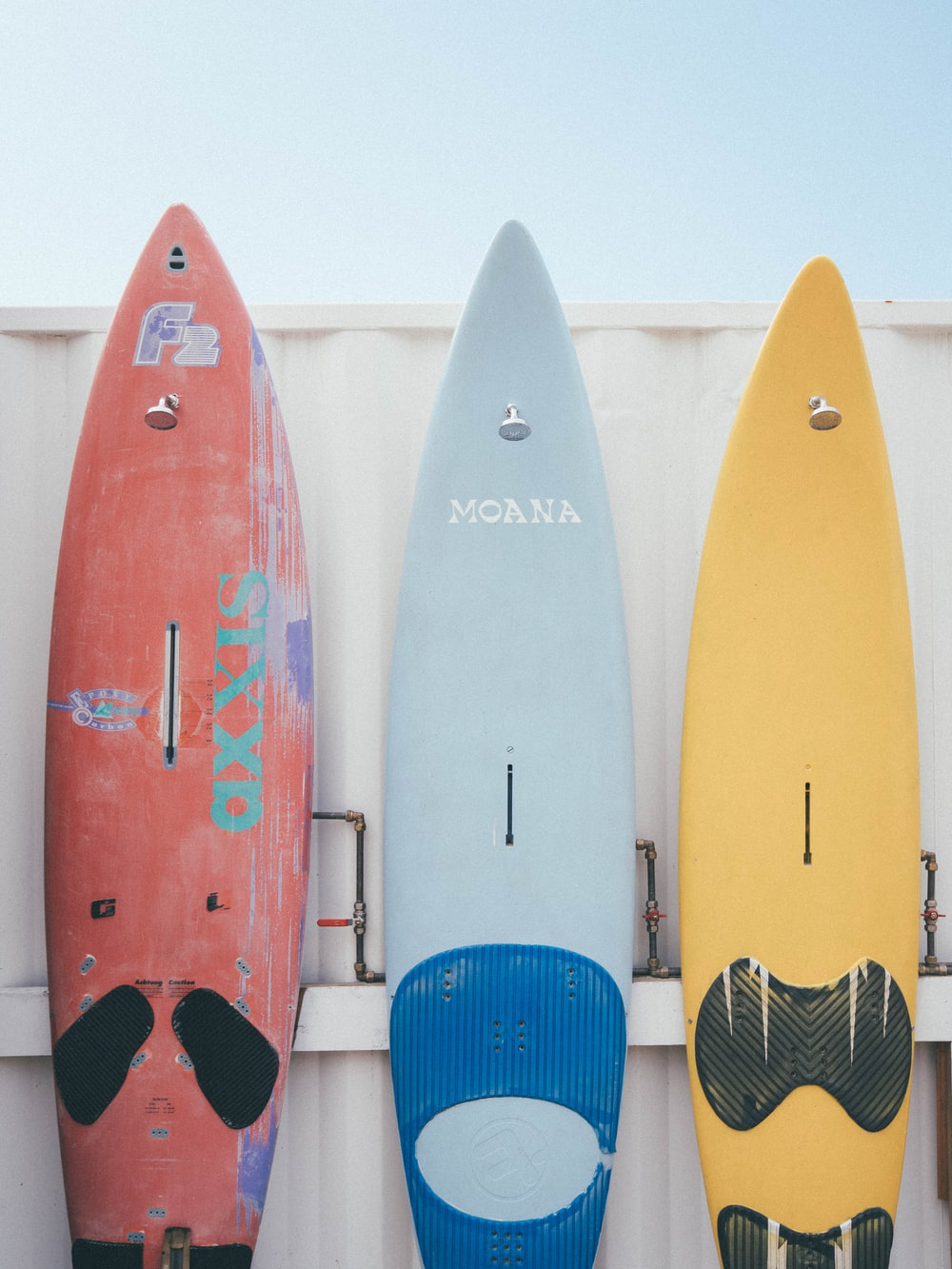 red and blue kayaks on white wooden fence