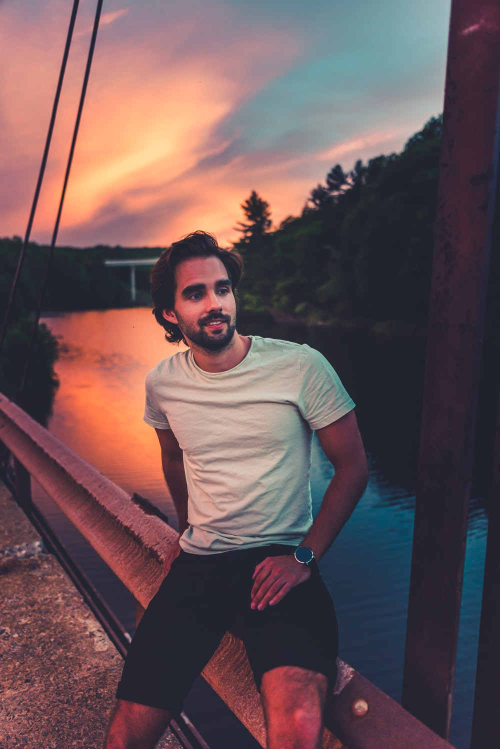 man in white crew neck t-shirt and black shorts standing on brown wooden bridge during