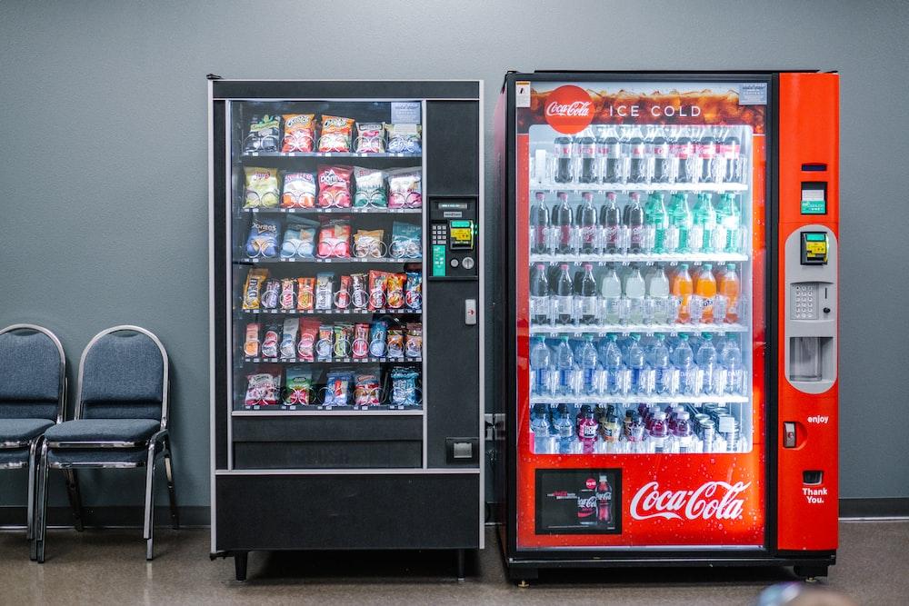 coca cola and coca cola bottles in black vending machine