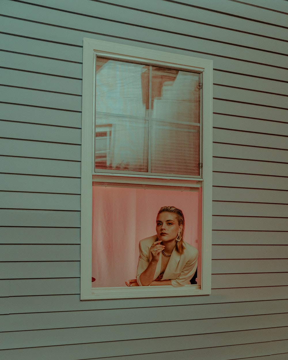 woman in white tank top standing in front of white wooden window