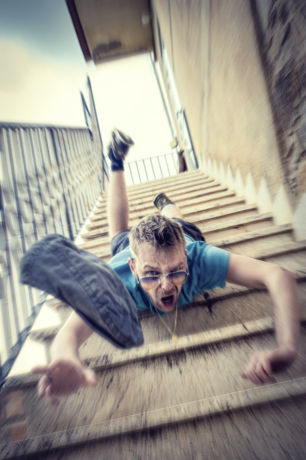 man in blue t-shirt and blue denim shorts sitting on concrete stairs during daytime