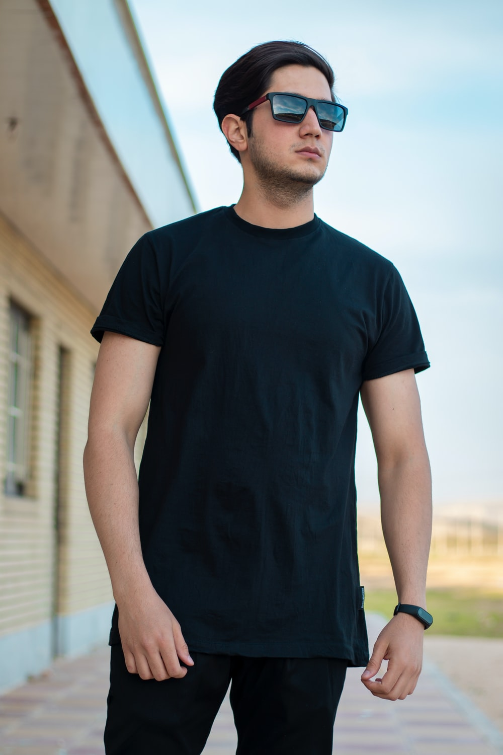 man in black crew neck t-shirt standing during daytime