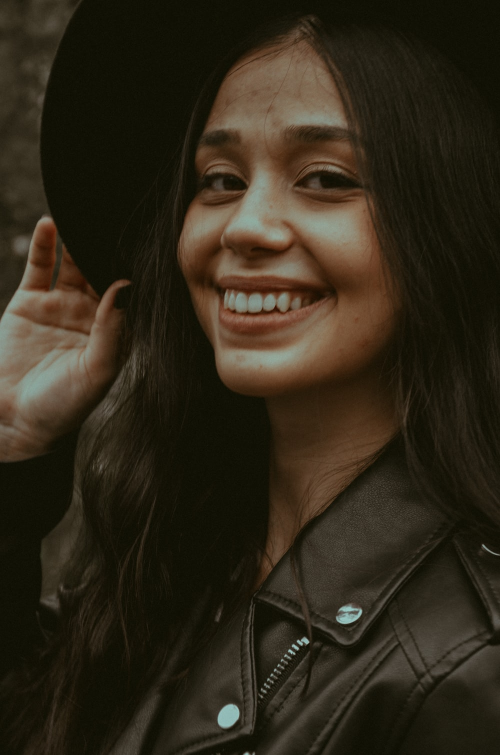 smiling woman in black leather jacket