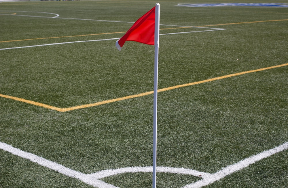 white and red flag on green field during daytime