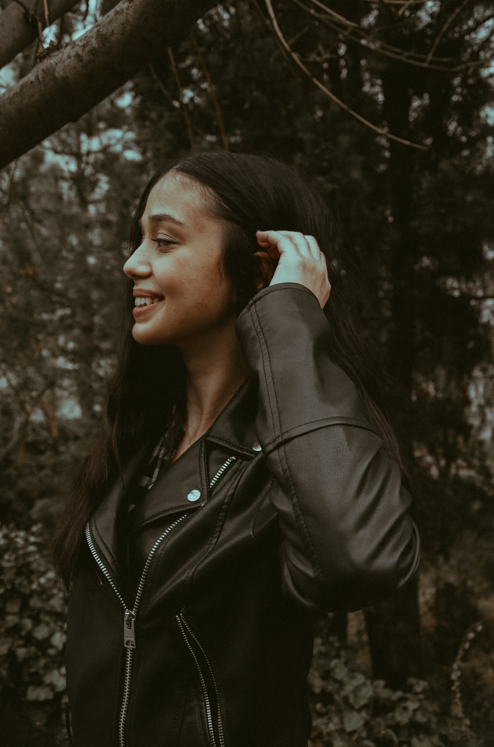 woman in black leather jacket standing near trees during daytime