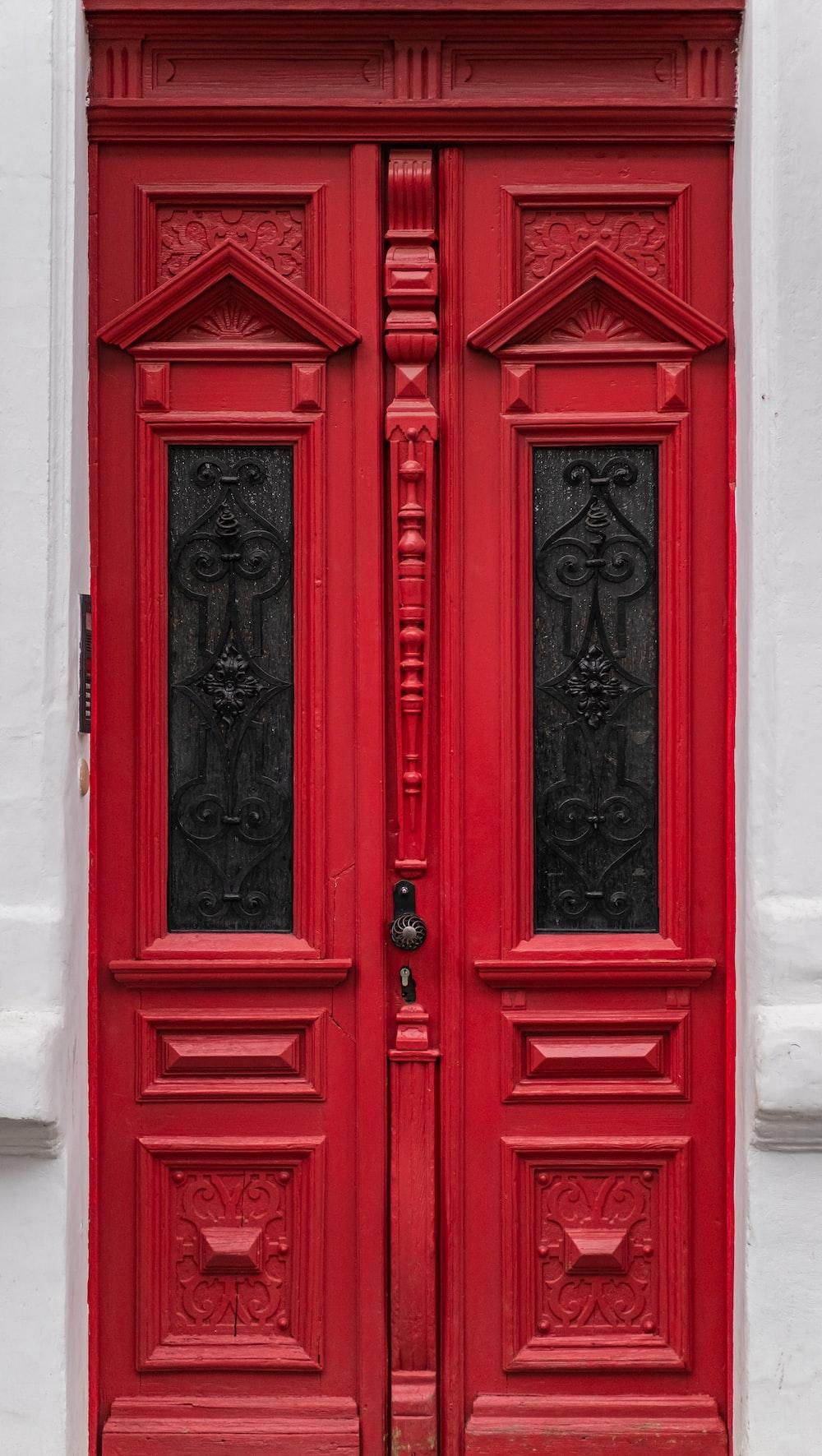 red wooden door with black steel door lever
