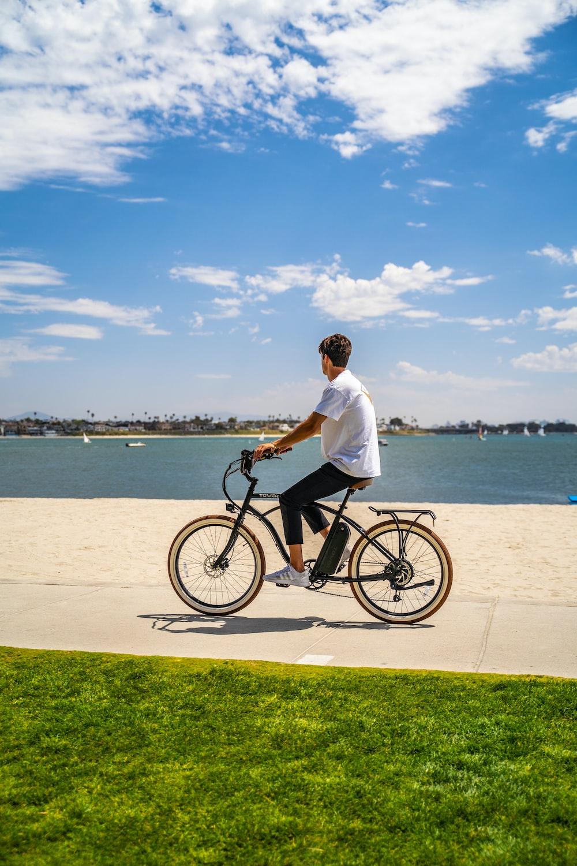 man in white dress shirt riding on black bicycle near sea during daytime