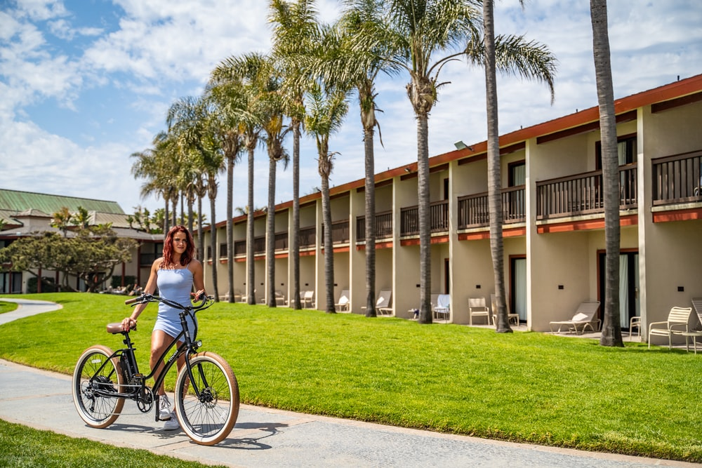 woman in blue tank top riding on black bicycle near white concrete building during daytime
