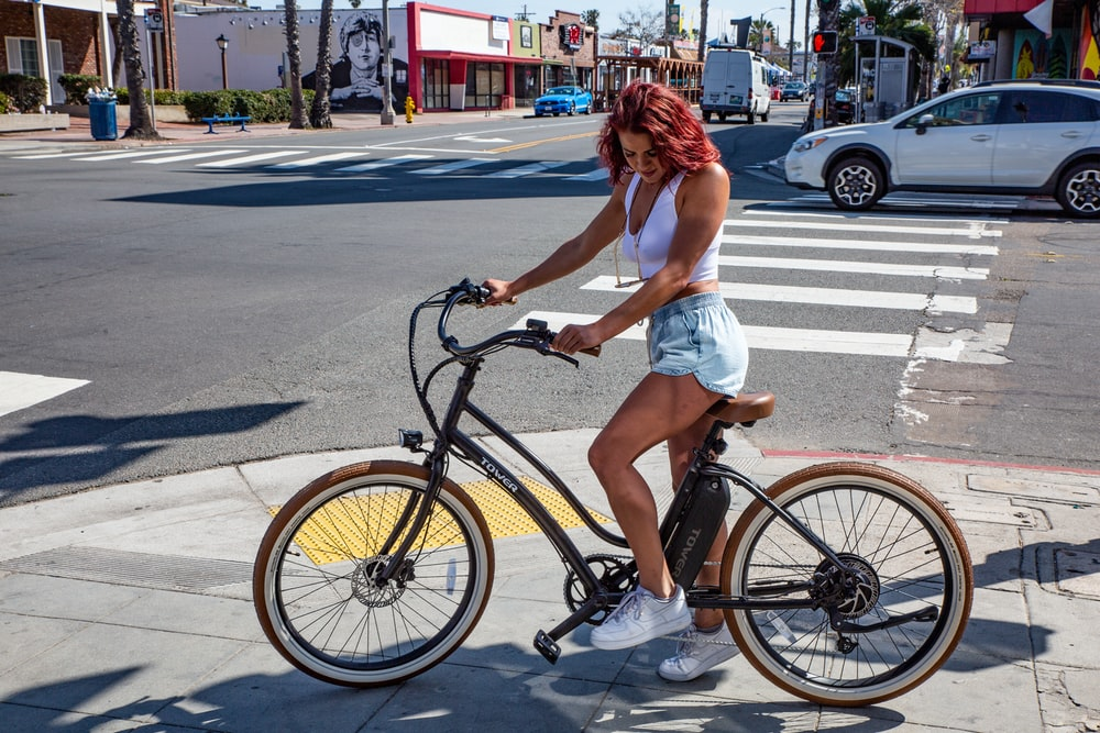 woman in white shirt riding on bicycle on road during daytime