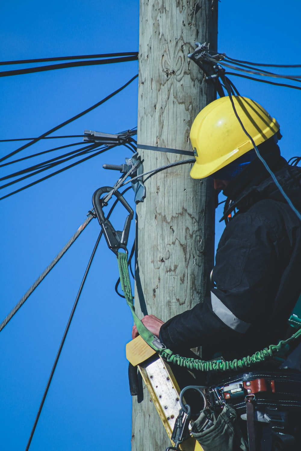 man in black jacket and yellow hard hat climbing on brown wooden post during daytime