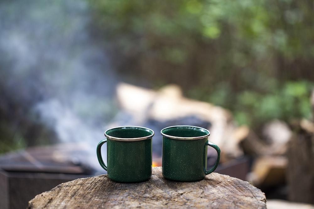 2 green ceramic mugs on brown wooden log