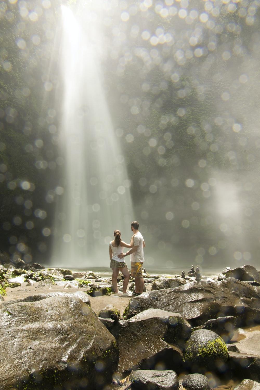 2 women standing on rock near water falls during daytime