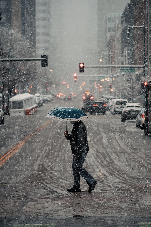 man in black jacket and pants holding umbrella walking on street during daytime