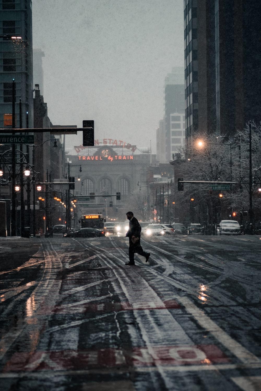 person in black jacket walking on pedestrian lane during daytime