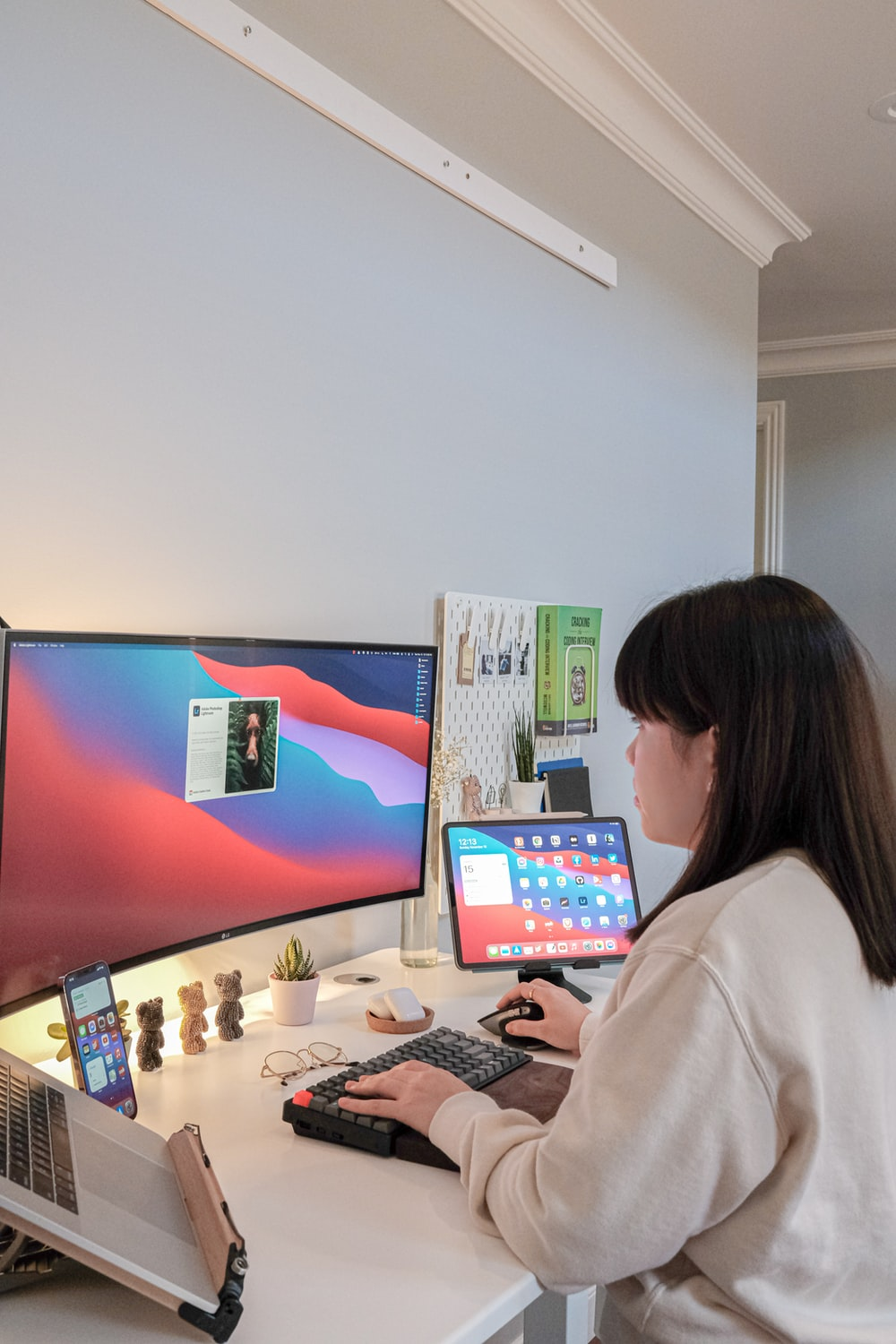 woman in white long sleeve shirt sitting in front of computer