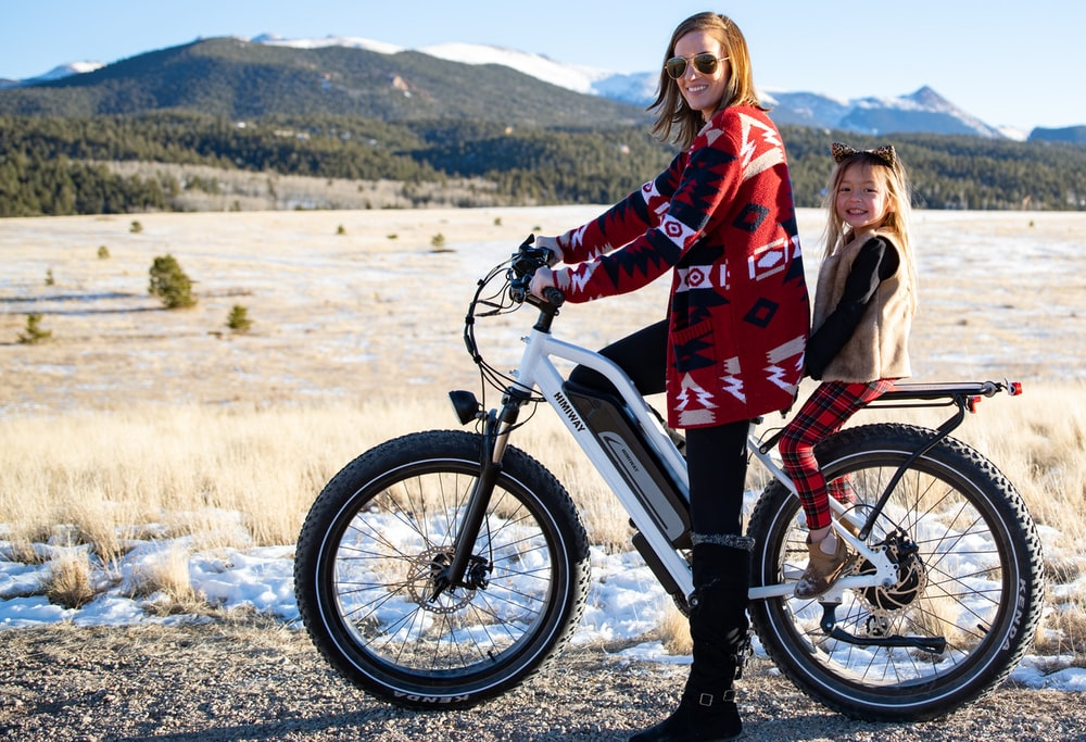 woman in red jacket riding on white and black mountain bike