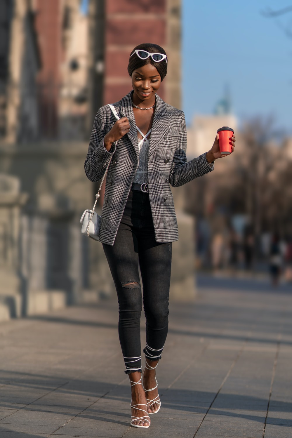 woman in gray blazer and black pants standing on road during daytime