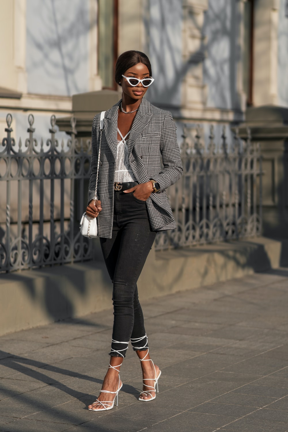 woman in gray blazer and black pants standing on gray concrete floor during daytime