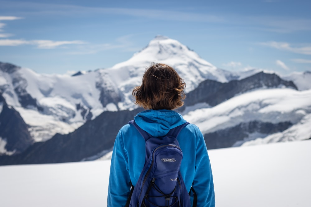 woman in blue jacket looking at snow covered mountain during daytime