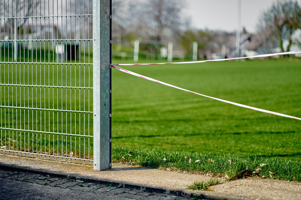 white metal fence on green grass field during daytime