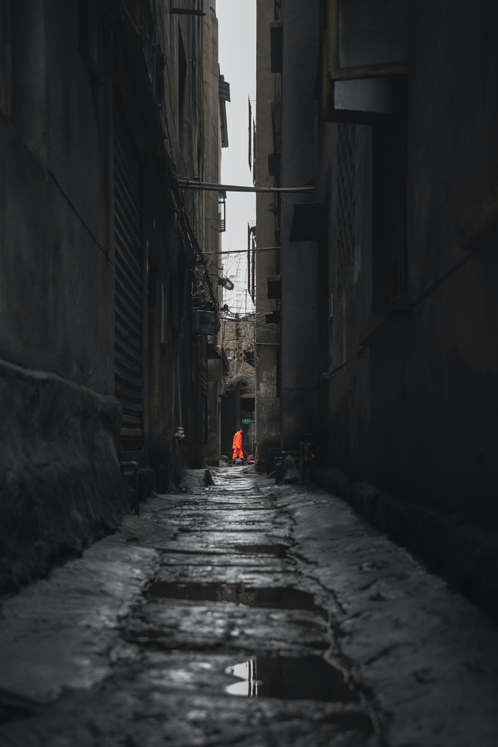 person in red jacket walking on street during daytime