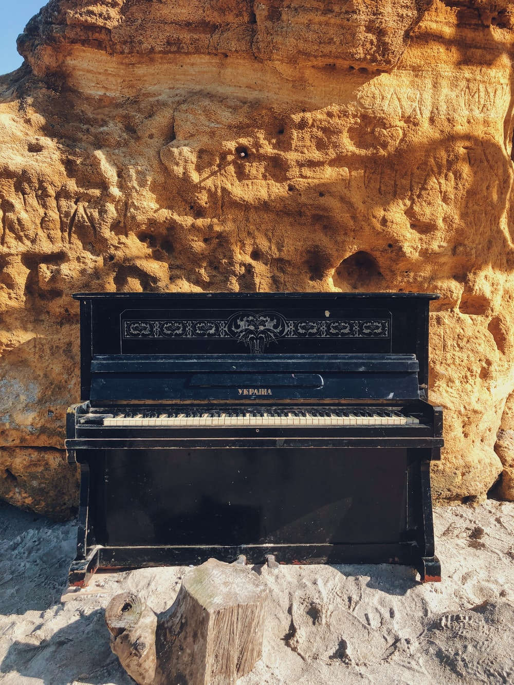 black upright piano beside brown wall