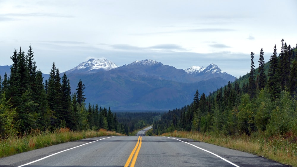 gray concrete road near green trees and mountains during daytime