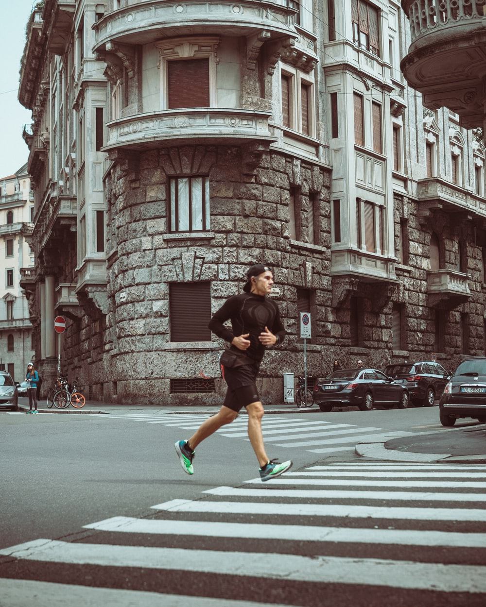 man in black t-shirt and green shorts running on pedestrian lane during daytime