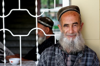 Dushanbe man in black and white plaid button up shirt wearing brown hat