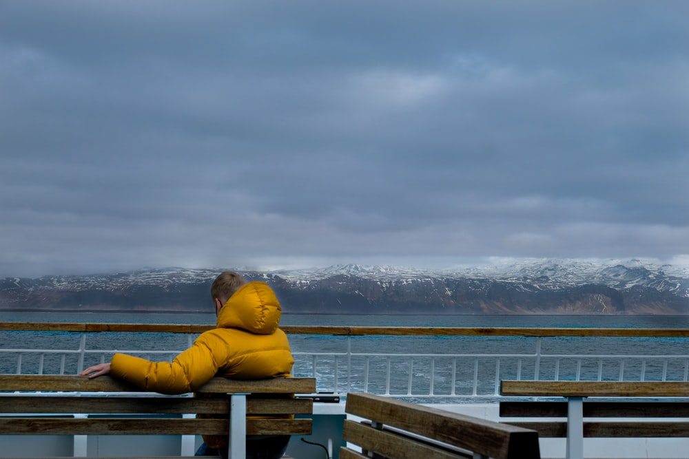 man in yellow hoodie sitting on brown wooden bench