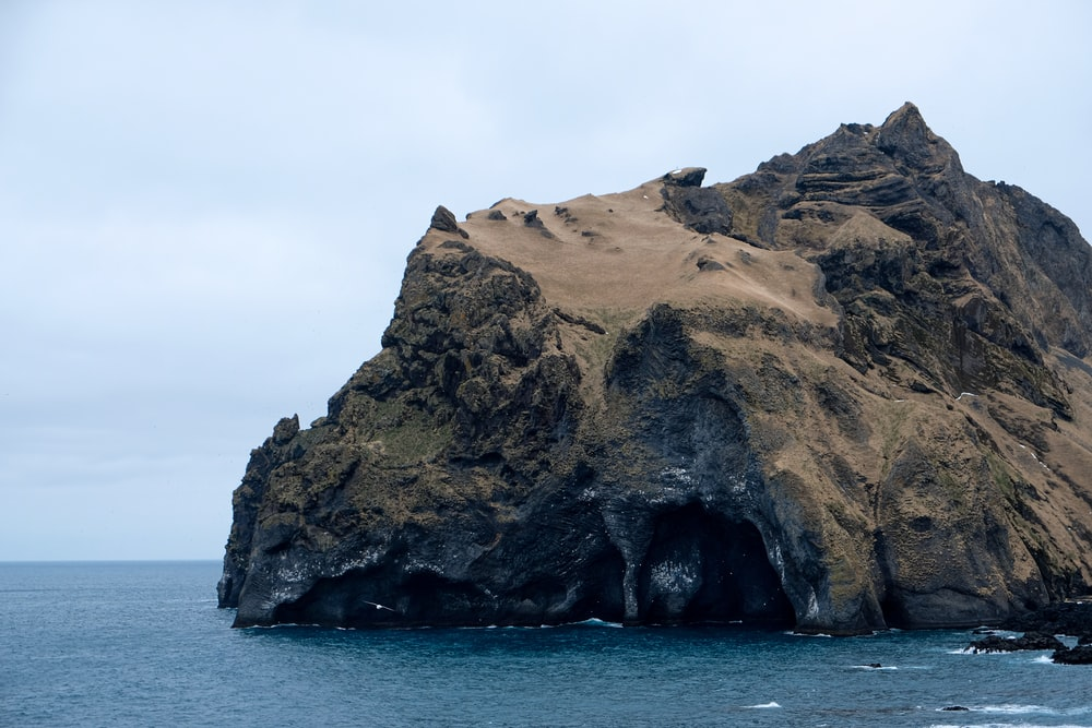 brown rock formation on blue sea under white sky during daytime