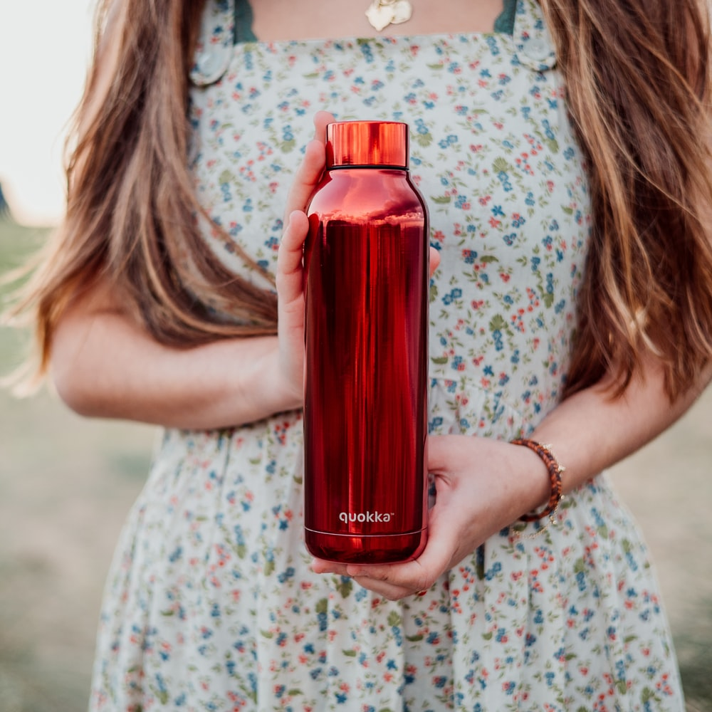 woman in white and pink floral dress holding red bottle