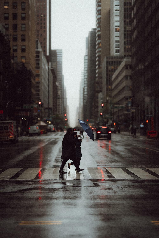 person in black jacket holding umbrella walking on pedestrian lane during daytime