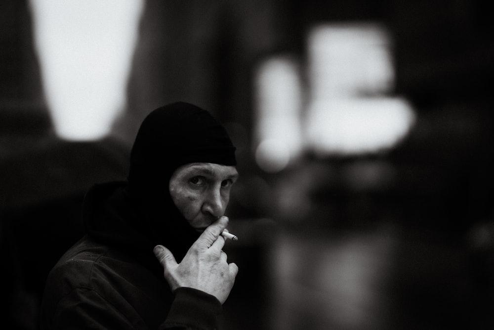 man in black knit cap smoking cigarette