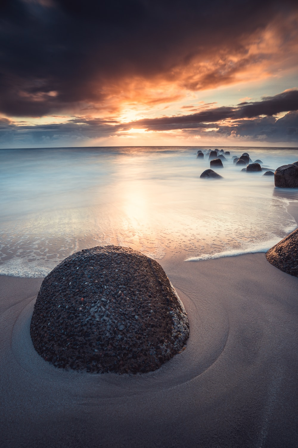 brown rock formation on seashore during sunset