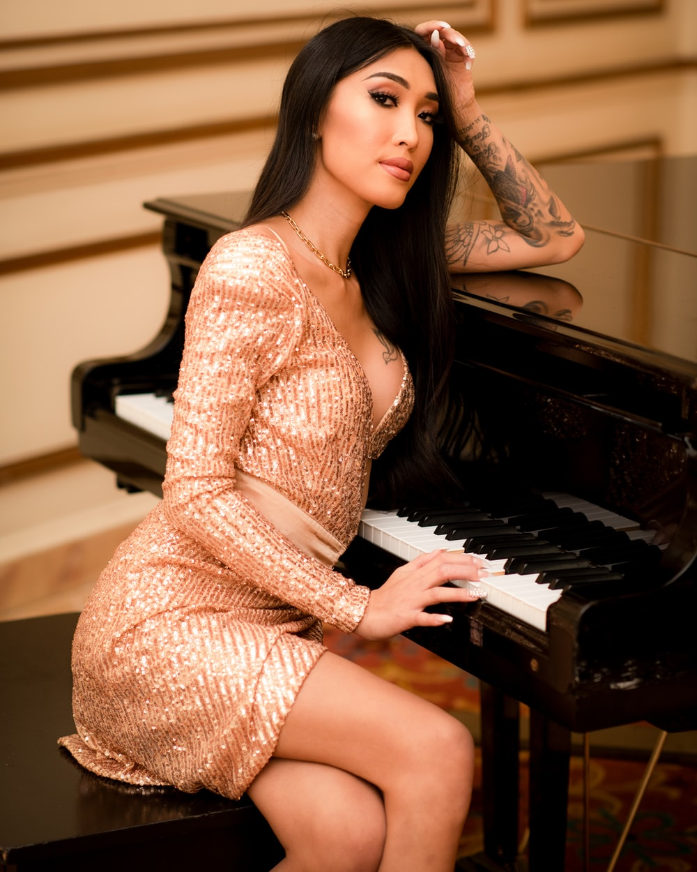 woman in white and brown dress sitting on piano