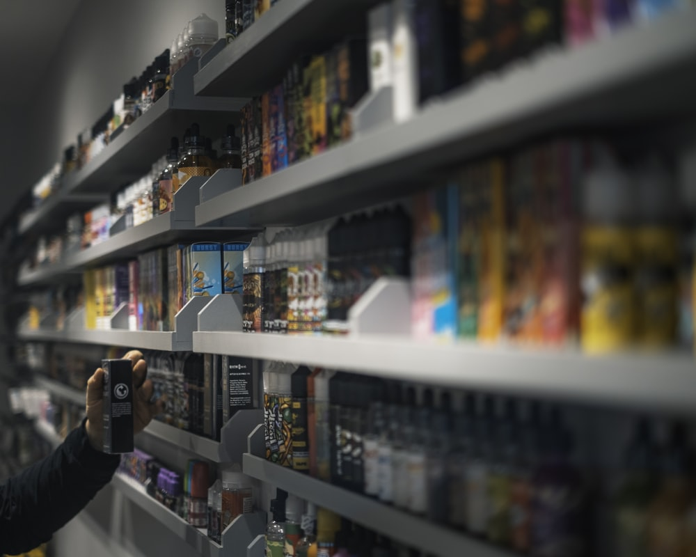 woman in black shirt standing in front of store shelf