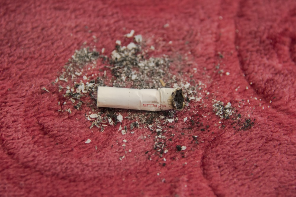 white cigarette stick on red textile